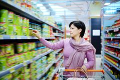 Woman pushing shopping cart choosing at goods in supermarket Stock Photo