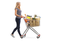 Woman pushing a shopping cart full of groceries. Full length portrait of a young woman pushing a shopping cart full of groceries isolated on white background Royalty Free Stock Photography