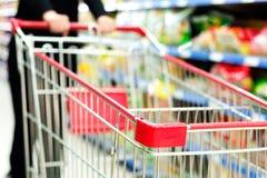 A woman pushing a shopping cart Stock Photos