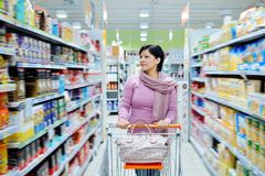 Woman pushing shopping cart looking at goods in supermarket Stock Photos