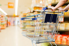 Woman pushing shopping cart Royalty Free Stock Images