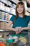 Woman pushing a shopping trolley Royalty Free Stock Photo