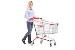 Woman pushing a shopping trolley. Full length portrait of a woman pushing a shopping trolley isolated on white background Royalty Free Stock Image