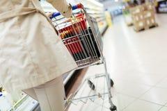 Woman pushing shopping trolley Royalty Free Stock Image
