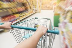 Woman pushing shopping trolley in supermarket Stock Photos