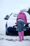 Woman pushing snow covered car in snowfall Royalty Free Stock Images