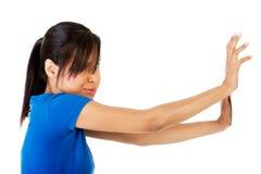 Woman pushing something imaginary Stock Images