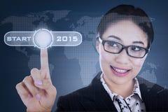 Woman pushing start button. Young hispanic woman pushing start button on a virtual screen to future 2015 Royalty Free Stock Image