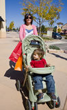 Woman pushing stroller Royalty Free Stock Photos