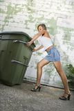 Woman pushing trash can. Stock Image
