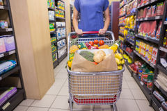 Woman pushing trolley in aisle Royalty Free Stock Photos