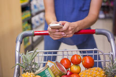 Woman pushing trolley in aisle and texting Stock Image