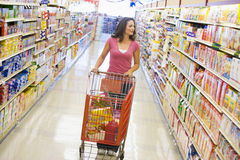 Free Woman Pushing Trolley Along Supermarket Aisle Stock Image - 5095351