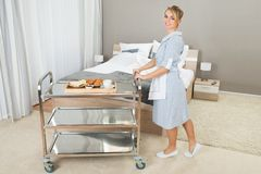 Woman pushing trolley with breakfast Royalty Free Stock Image