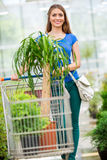 Woman pushing the trolley through a store flowers. Royalty Free Stock Photos