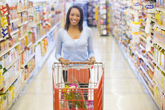 Woman pushing trolley in supermarket. Woman pushing trolley along aisle in supermarket Royalty Free Stock Photo
