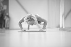 Woman pushing up in the gym, monochrome Royalty Free Stock Image