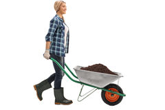 Woman pushing a wheelbarrow with dirt royalty free stock photography