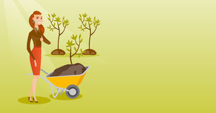 Woman pushing wheelbarrow with plant. Royalty Free Stock Photography