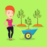 Woman pushing wheelbarrow with plant. Royalty Free Stock Photo