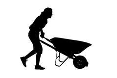 Woman Pushing Wheelbarrow. Woman working in her yard pushing a wheelbarrown Royalty Free Stock Image