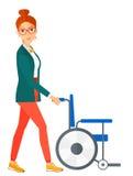 Woman pushing wheelchair Royalty Free Stock Image