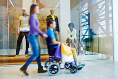 Woman Pushing Wheelchair Husband in Mall. Motion image of women wheeling handicapped men past shopping windows with mannequins display in mall during day of Stock Photos