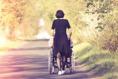 A woman pushing a wheelchair taking care of a disabled person royalty free stock photography