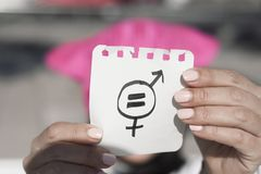 Woman with pussyhat and symbol for gender equality. Closeup of a young woman outdoors, wearing a pink pussycat hat, showing a piece of paper in front of her face Stock Photos