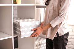 Woman put a cardboard box on shelf. stock images