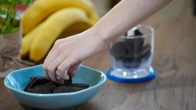 Woman put chocolate cookies in the blender. Cooking process.  stock video