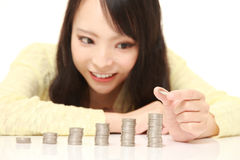 Woman put coins to stack of coins Stock Photos