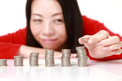 Woman put coins to stack of coins Stock Photography