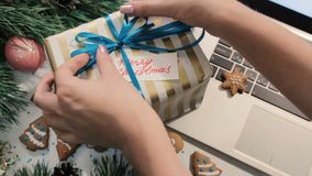 Woman put congratulation memo to gift box. Top view. Christmas and New Year presents and greetings concept stock footage