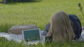 Woman put eyeglasses on face and uses digital tablet relaxing on blanket in park. Young woman is relaxing on blanket in park and uses digital tablet. The female stock video footage