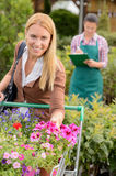 Woman put flowers in shopping cart greenhouse Stock Photos