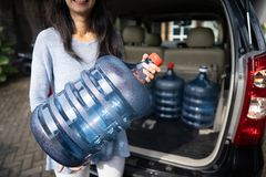 Buying a new gallon of water. Woman put a gallon of water in the car trunk at home. wanted to purchase the refill or by the new one stock photography