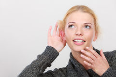 Woman put hand to ear for better hearing. Gestures, gossip and rumors, hearing loss or disorder. Woman put hand to ear for better hear having hand on mouth Royalty Free Stock Photography
