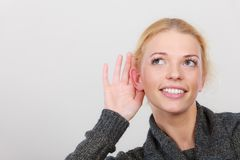Woman put hand to ear for better hearing. Gestures, gossip and rumors, hearing loss or disorder. Woman put hand to ear for better hear. Studio shot on light grey royalty free stock images