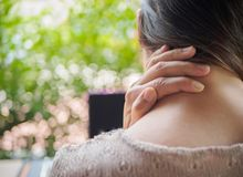 Woman put her hand on the back of her neck while feeling pain. After long hours work on computer. Office syndrome concept Stock Photos