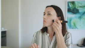 A middle-aged woman in the room in front of the mirror making herself a makeover. stock footage