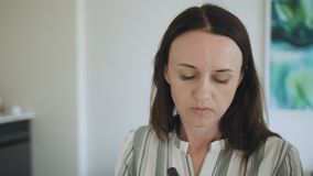 A middle-aged woman in the room in front of the mirror making herself a makeover. stock video