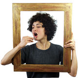 Woman put lipstick on through picture frame Stock Photo