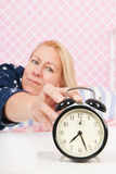Woman put out the alarm clock Royalty Free Stock Photos