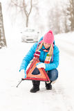 Woman put reflector triangle car breakdown winter Stock Image