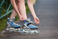 Woman put on roller-skate close up Royalty Free Stock Photo