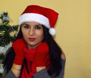 The woman put on Santa`s cap. The beautiful woman put on Santa`s cap, a red scarf and gloves Stock Images