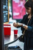 Woman put sugar in red paper coffee cup. Urban lifestyle stock photography