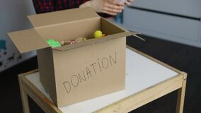 Woman put used toys in cardboard box for donation