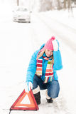 Woman put warning triangle car breakdown winter Stock Photography